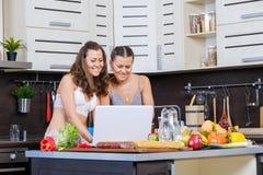 Deux soeurs jumelles recherchant la recette de salade sur l'Internet Images libres de droits