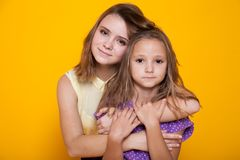 Deux soeurs, l'embrassement d'aîné plus jeune images stock