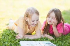Deux soeurs lisant dehors, ayant l'amusement Image stock
