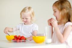 Deux soeurs mangeant de la céréale avec du lait Photographie stock