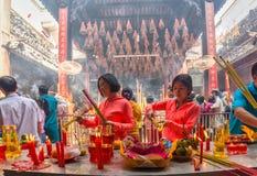 Deux soeurs ont brûlé le jour de nouvelle année lunaire de paix de Bouddha de culte d'encens Photographie stock