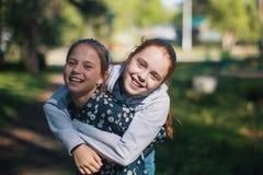 Deux soeurs ou amies de filles ayant l'amusement dehors Images stock