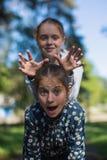 Deux soeurs ou amies de filles ayant l'amusement dehors Image stock