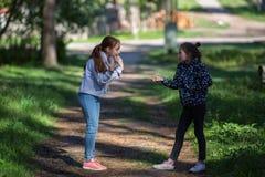 Deux soeurs ou amies de filles parlent avec émotion dehors nature Images stock