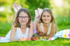 Deux soeurs ou amis mignons dans un jardin de pique-nique se trouvent sur une plate-forme et mangent les cerises fraîchement séle Photographie stock libre de droits