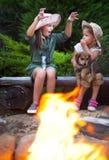 Deux soeurs parlant des histoires par le feu de camp Photos libres de droits