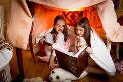 Deux soeurs s'asseyant dans la maison faite de couvertures et livre de lecture Images stock