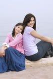 Deux soeurs s'asseyant par la plage Photographie stock libre de droits