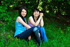 Deux soeurs s'asseyant sur l'herbe Photos libres de droits