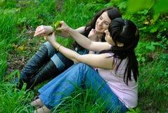 Deux soeurs s'asseyant sur l'herbe Images stock