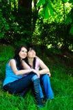 Deux soeurs s'asseyant sur l'herbe Photo libre de droits