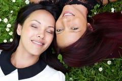 Deux soeurs se trouvant sur l'herbe et le sourire Images libres de droits