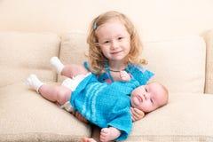 Deux soeurs Un enfant plus âgé de soeur étreignant sa petite soeur nouveau-née Photo stock