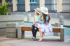 Deux soeurs, une belle fille de brune et une jeune fille marchant dans la ville, s'asseyant sur un banc et parlant, riant Images libres de droits