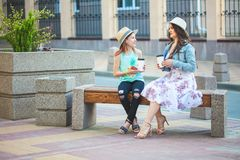 Deux soeurs, une belle fille de brune et une jeune fille marchant dans la ville, se reposant sur un banc avec du café dans des ma Images libres de droits