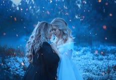 Deux sorcières sont foncées et légères pressées les uns contre les autres Autour de eux flashes de la magie avec des étincelles,  Photo stock