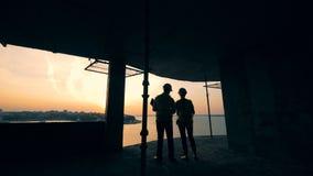 Deux spécialistes en construction parlant dans une maison de bâtiment dans le coucher du soleil banque de vidéos