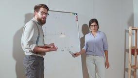 Deux spécialistes expliquent aux associés un rapport, montrant des diagrammes banque de vidéos