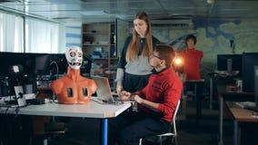 Deux spécialistes manoeuvrent des mouvements du visage du robot à distance banque de vidéos