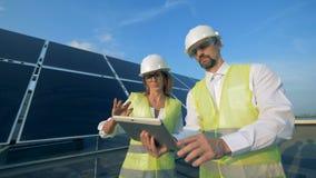 Deux spécialistes solaires sont marchants et actionnants leur comprimé tout en parlant clips vidéos