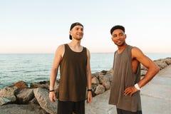 Deux sportifs de sourire se tenant dehors à la plage Photos libres de droits
