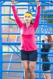 Deux sportives caucasiennes dans l'équipement extérieur d'été ayant des exercices sur les anneaux sur le champ photos stock