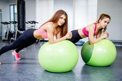 Deux sportives heureuses s'exerçant avec une boule faisant la planche s'exercent dans le gymnase Image stock