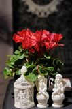 Deux statuettes des anges et des fleurs rouges Images stock