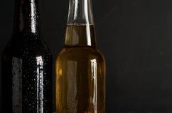 Deux suant, bouteille froide de plan rapproché de bière sur le fond noir Photos libres de droits