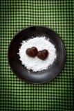 Deux sucreries en forme de coeur de chocolat d'un plat brun avec la poudre de sucre contre le vert ont vérifié le fond de tissu Photos libres de droits