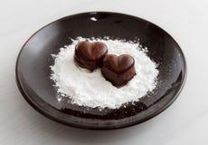 Deux sucreries en forme de coeur de chocolat d'un plat brun avec la poudre de sucre sur le fond en bois Photos stock