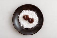 Deux sucreries en forme de coeur de chocolat d'un plat brun avec la poudre de sucre sur le fond en bois Photographie stock