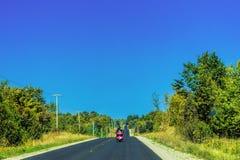Deux sur une moto sur une nouvelle route Photos libres de droits