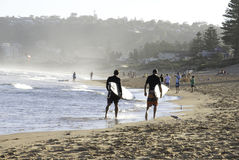 Deux surfers marchant le long d'une plage Images libres de droits