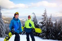 Deux surfeurs marchant à la station de sports d'hiver Amis s'élevant jusqu'au dessus de montagne portant leurs surfs des neiges p photos libres de droits