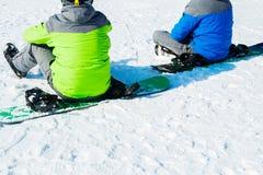 Deux surfeurs s'asseyent sur la neige en haut de la montagne et examinent la distance Vue par derrière photographie stock