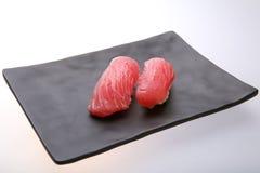 Deux sushi frais de thon sur un plat noir Images stock