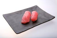 Deux sushi frais de thon sur un plat noir Photo stock