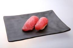 Deux sushi frais de thon sur un plat noir Photographie stock libre de droits