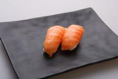 Deux sushi saumonés frais sur un plat noir Photos stock