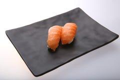 Deux sushi saumonés frais sur un plat noir Photo libre de droits