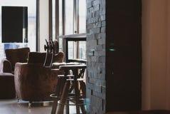 Deux swirly chaises d'arbitre placées sous la table en bois de longue barre dans le lat photographie stock libre de droits