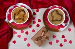 Deux tasses avec des coeurs de café, de boîte-cadeau et de papier fond romantique Photos libres de droits