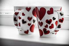 Deux tasses avec des coeurs sur le filon-couche d'une fenêtre Photos libres de droits