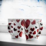 Deux tasses avec des coeurs sur le filon-couche de fenêtre d'un congelé Images stock
