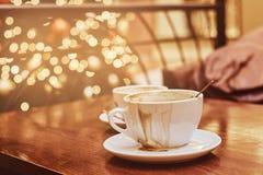 Deux tasses avec du café renversé sur la table en bois dans un café, fond de tache floue avec l'effet de bokeh photos libres de droits