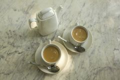 Deux tasses blanches avec le thé de lait, les cuillères et une théière en céramique sur la surface de marbre du plan rapproché de photos libres de droits