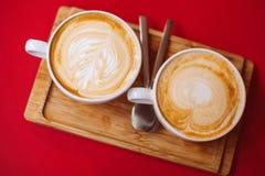 Deux tasses blanches de café chaud de latte de café de cappuccino sur la table rouge en café photos libres de droits