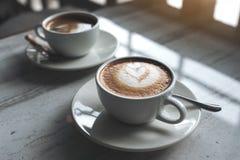 Deux tasses blanches de café chaud sur la table en café Images libres de droits