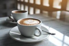 Deux tasses blanches de café chaud sur la table en café Photos stock